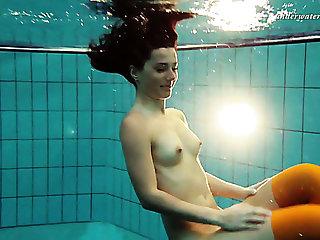 Slim brunette girl Nina Markova swimming bare in a pool